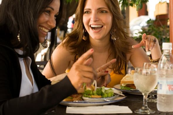 Side profile of two women sitting in a restaurant and smiling, Santo Domingo, Dominican Republic