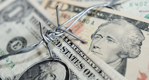 Concept Barbed wire and US Dollars Financial security.