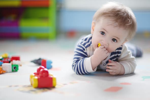 9 month old baby boy lying on his belly, playing with toy bricks, putting one in his mouth