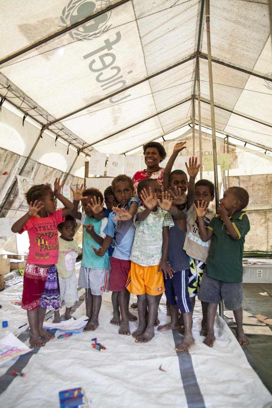 Kids from Loubukas Kindergarten sing and dance under the cover of a UNICEF tent after their schoolhouse...