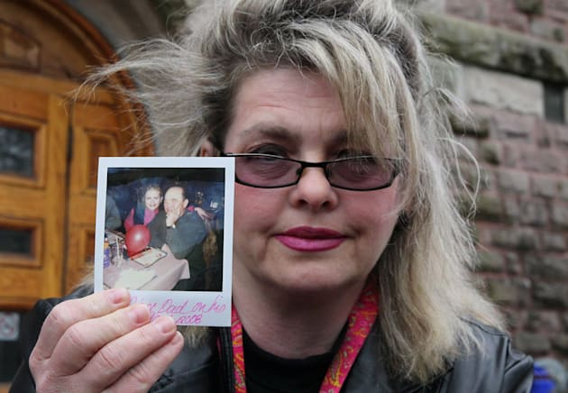 Susan Horvath, daughter of victim Arpad Horvath, holds a photo of her father from his 70th birthday as...