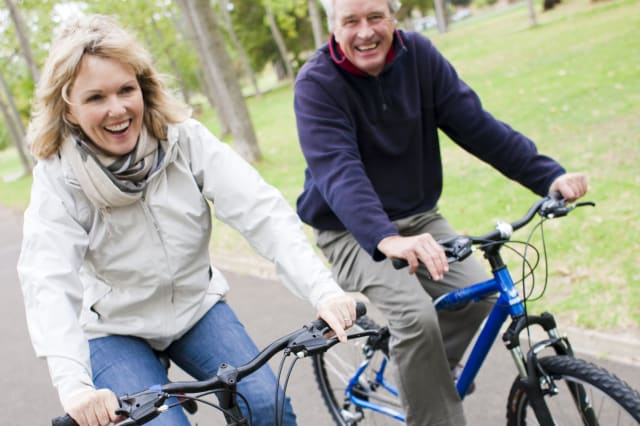 Senior couple having fun together while cycling on bikes.