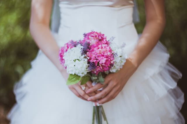 Close-up picture of young bride's hands in white wedding dress holding flower bouquet of pink and lilac colors.