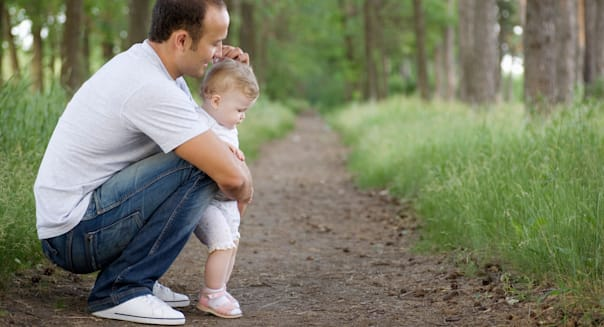 BF1FGX A father crouching with his baby daughter on a rural path. life insurance A; father; crouching; his; baby; daughter; on;