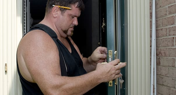 Contractor installing new doors on residential home
