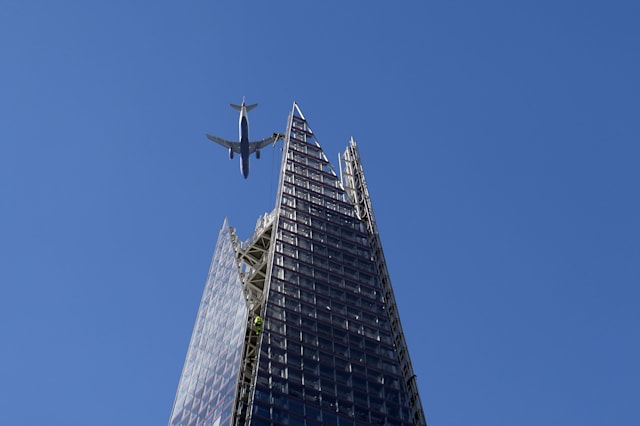 The Shard buidling Europe's highest building on sunny day with planes flying overhead.