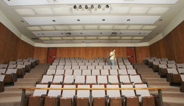 Student walking in empty classroom auditorium