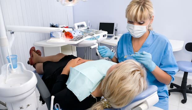 doctor works with patient in the dentist office