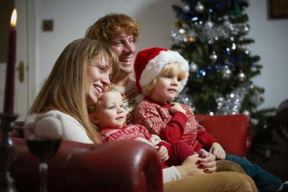Young family in living room watching television on Christmas day.