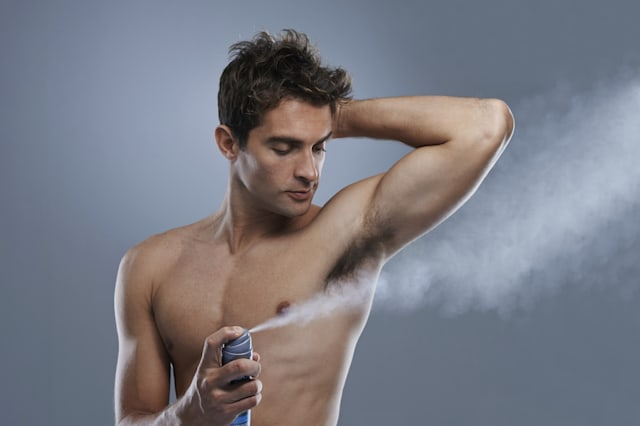 A muscular young man spraying his underarms with deodorant