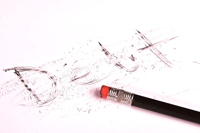 AH3E2R Black pencil is erasing the word Debt from a piece of white paper. Conceptual image for getting out of debt. debt; credit