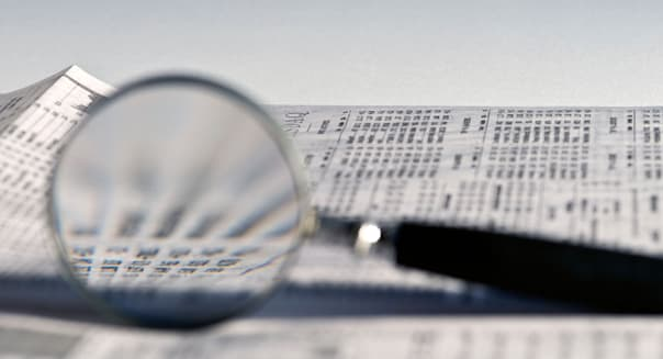 BKKG0N Magnifying glass highlighting stock quotes in business section of newspaper. Magnifying; glass; stock; business; section;