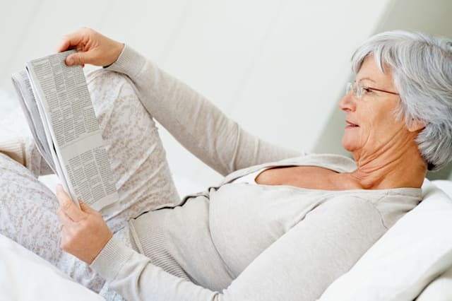 C4T88N Retired smiling senior woman reading newspaper on the bed at home