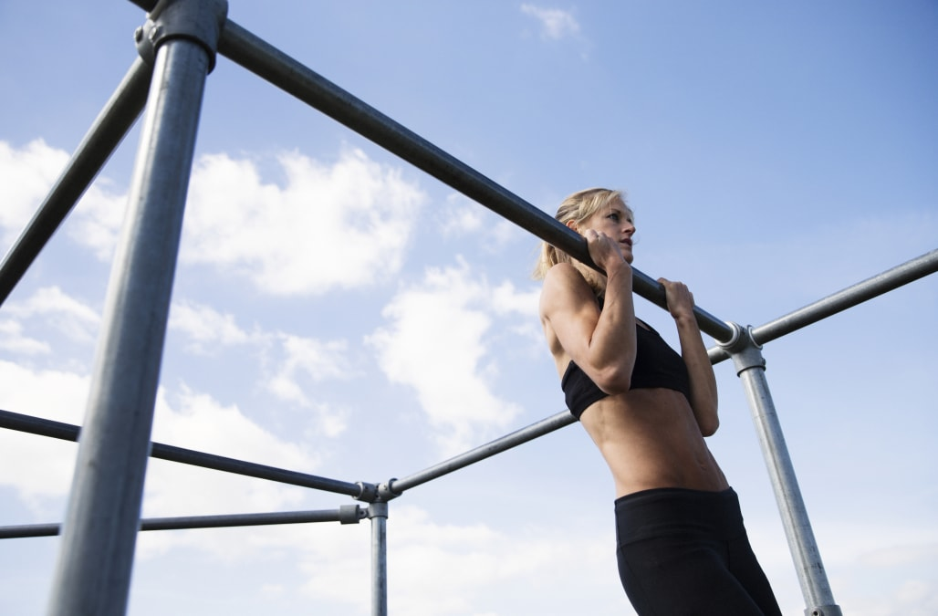Woman doing chin-ups outside
