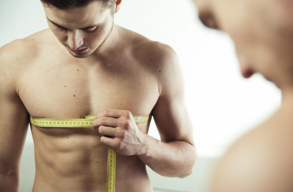 Close-up of young man reflected in bathroom mirror, measuring chest with tape measure, studio shot on white background