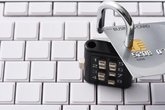 Close-up of credit card with unlocked padlock on computer keyboard