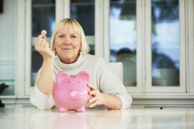 portrait of happy caucasian senior woman saving euro coin into piggybank and smiling at camera