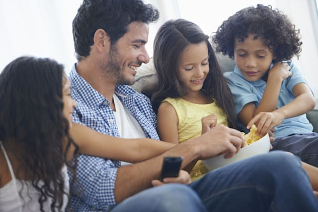 Shot of a family eating popcorn while sitting on a sofa and watching tv