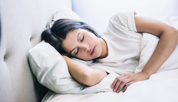 woman eyes closed laying in bed