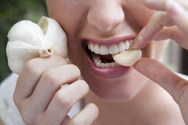 close up of woman biting into a garlic clove
