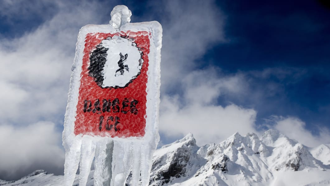 Danger sign with icicles in front of snow covered mountains