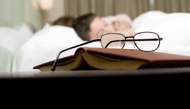 Eyeglasses and book on nightstand