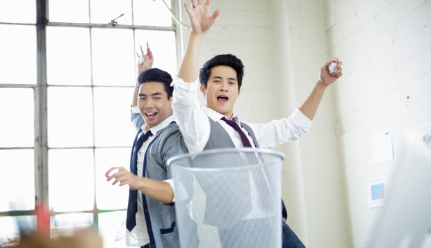 Two young men celebrating target practice in office