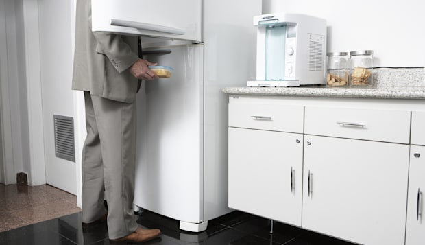 Man removing food from refrigerator in office kitchen, low section