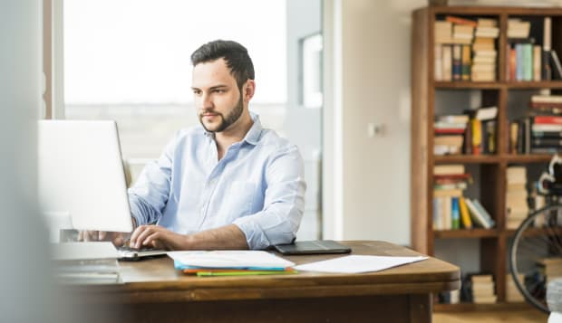Young man working at computer at home