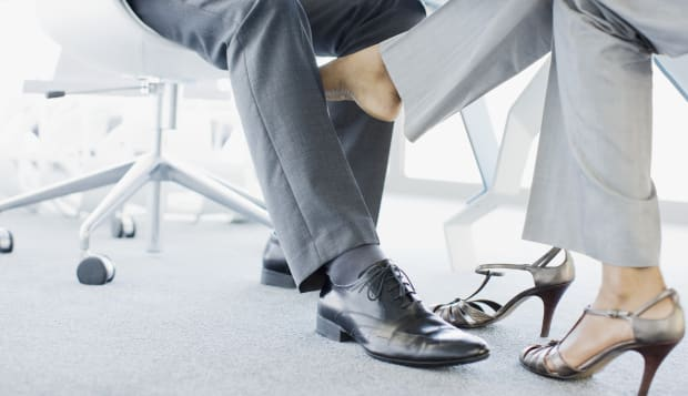 Businesswoman playing footsie with co-worker