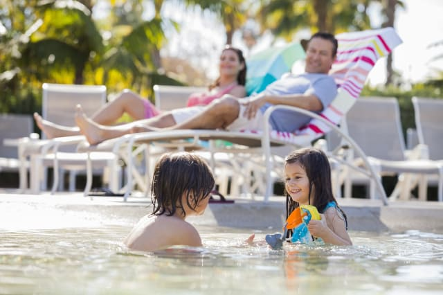 Siblings playing in pool at resort while parents sit in  background