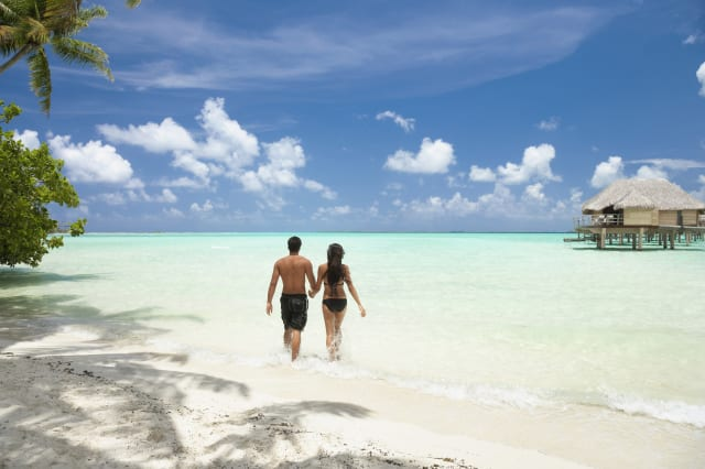 Pacific Islander couple walking on tropical beach