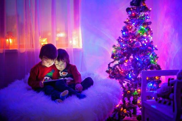 Two boys, playing on tablet at home, next christmas tree