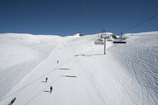 Chairlift above skiers on piste