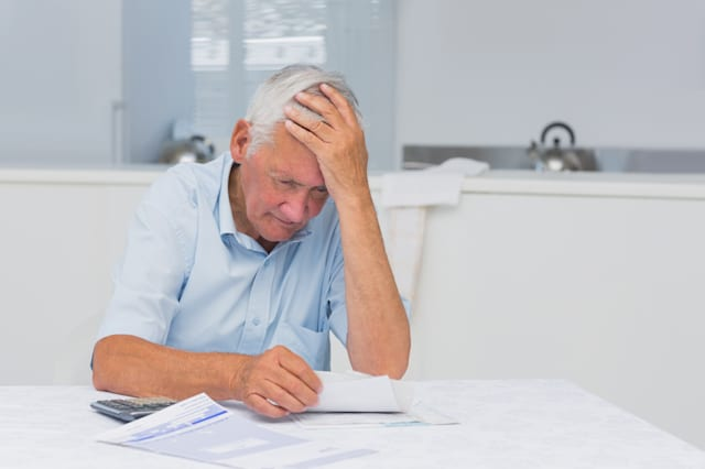 Elderly man feeling anxious about his bills at home