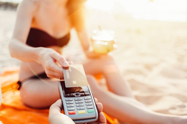 Woman on the beach making contactless credit card payment   ++++ Note for the inspector: Credit card is fake ++++