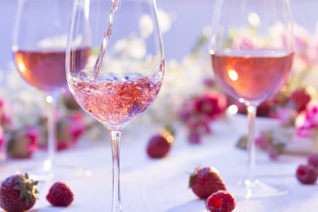 Glass of rosé wine being poured at a picnic setting on a summer's day.