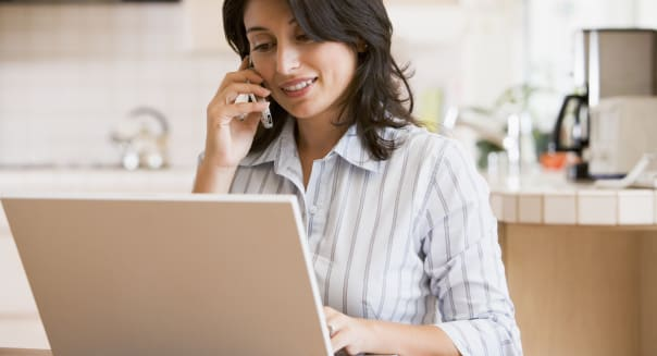 Woman in kitchen with laptop using cellular phone smiling