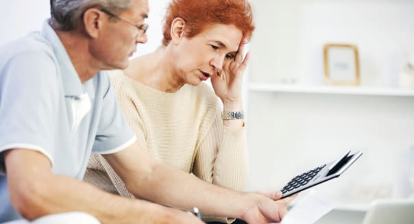Senior couple calculating their monthly finances at home.