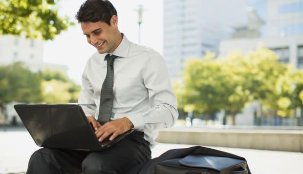 Smiling businessman working on laptop in urban park