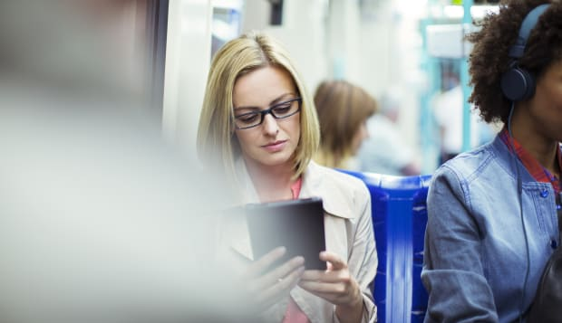 Businesswoman using digital tablet on train
