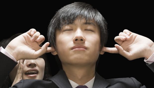 Businessman covering his ears with his fingers,  businesswoman speaking behind him