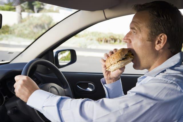 Man eating and driving car