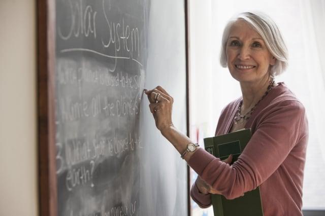 Caucasian teacher writing on chalkboard