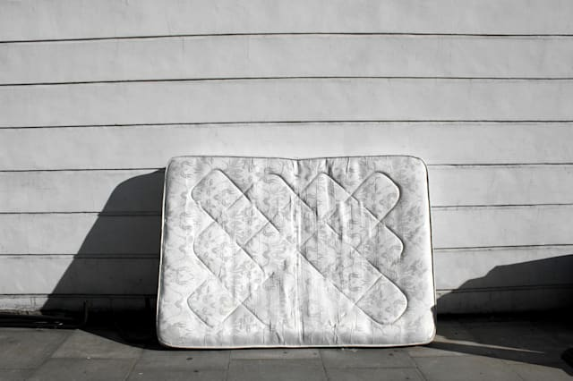 Old mattress leaning up against wall on street.