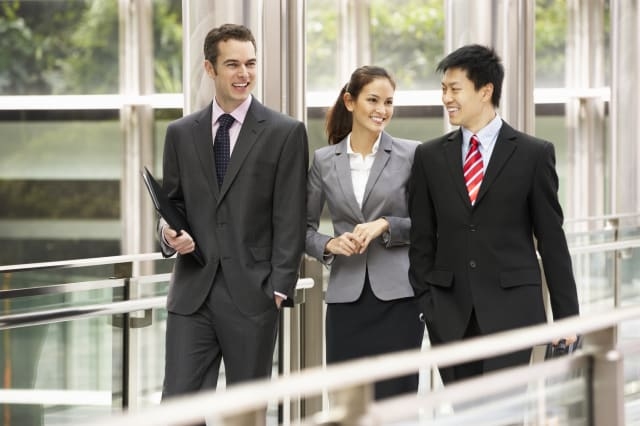 Three Business Colleagues Having Discussion Whilst Walking Outside Office
