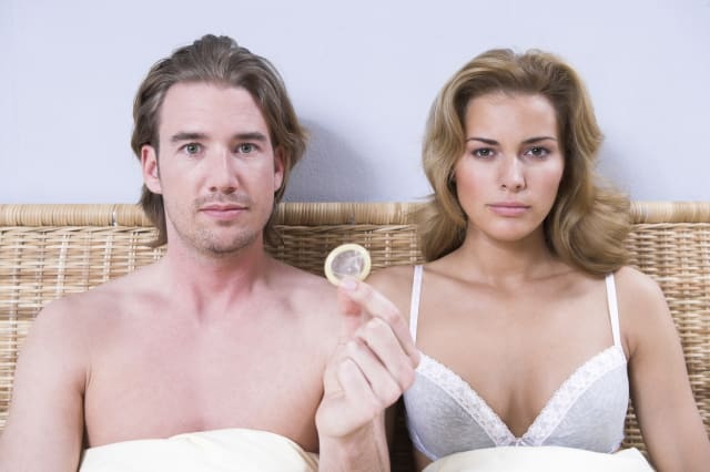 portrait of young couple sitting in bed man holding condom