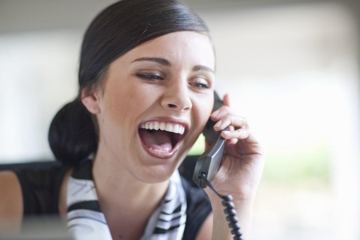 Young office worker talking on landline handset