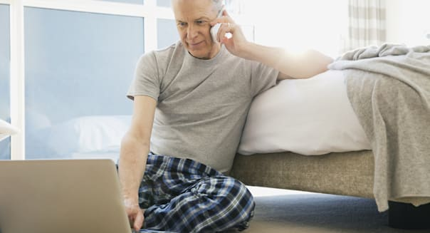 Man using cell phone and laptop in bedroom