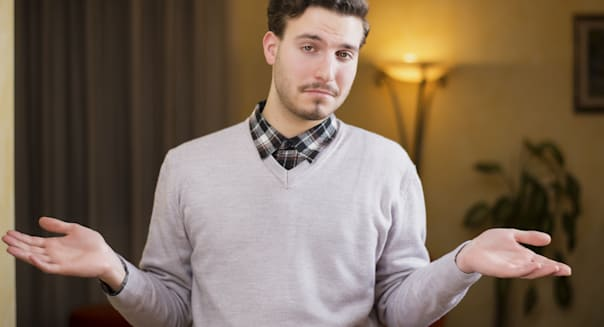 Confused or doubtful young man shrugging with palms open, indoor shot in a house